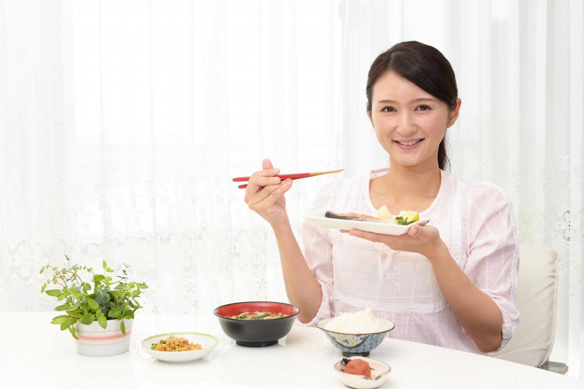 ご飯を食べる女性の写真